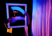 Young girl with glowing hat, frame and curtain.Black light