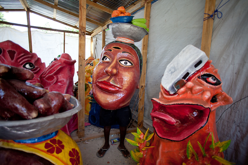 The carnival celebrations in Jacmel are famous for intricate paper mache masks and street theater. Carnival celebrations did not happen last year in Haiti becuase of the January 12th earthquake. For many of the artisans in Jacmel the revenue from carnival is their primary source of income./// Artist Barthelemy Harrison puts on one of his masks in his shop. The mask on the right is on the subject of earthquake damage, the charachter got hit with a block from a collapsing house.