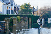 © Licensed to London News Pictures. 12/01/2014. Wraysbury, UK. A man walks home from shopping. Flooding in Wraysbury, Berkshire today 12th January 2014.  Flooding and property damage is expected to continue along the River Thames.  Large areas of Britain are experiencing flooding after wet weather. Photo credit : Stephen Simpson/LNP