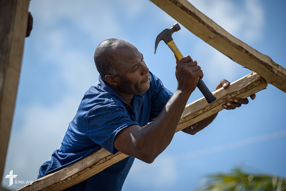 A man repairs a roof at a home damaged by Hurricane Matthew on Wednesday, Oct. 12, 2016, in Les Cayes, Haiti. LCMS Communications/Erik M. Lunsford