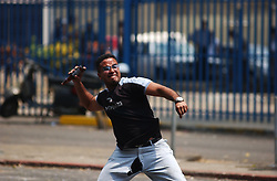 An anti-government protestors launches a bottle at the National Guard as riots continued in Caracas between the two groups. The country is awaiting a preliminary decision on the validity of signatures seeking a recall referendum.  It is expected that hundreds of thousands of signatures will have to go to a review process that the opposition will refuse to submit to.