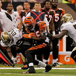 2009 August 14: New Orleans Saints defenders Jason David (29) and Jo-Lonn Dunbar (56) hit Cincinnati Bengals wide receiver Chris Henry (15) after a catch during a preseason opener between the Cincinnati Bengals and the New Orleans Saints at the Louisiana Superdome in New Orleans, Louisiana.
