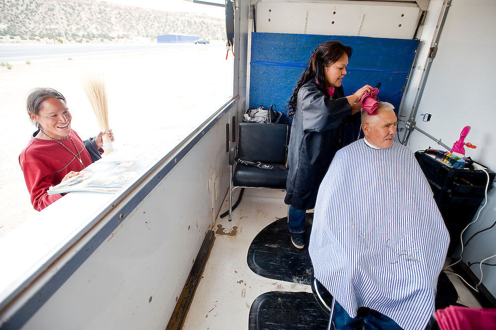 050912       Brian Leddy.Ophelia Keeto gives a haircut Lorenzo Redhouse on Wednesday in Tse Bonito. Keeto and her brother Virgil recently opened up a mobile haircutting salon in a trailer. The business travels the reservation and aims to raise money for elders that need assistance in paying their utility bills
