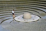 A boy explores spiral concrete fountain art in Darling Harbour precinct, Sydney, New South Wales (NSW), Australia.