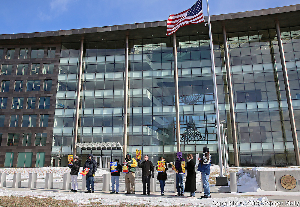 Nine people hold up signs at a rally organized by the Hawkeye Labor Council and the AFL-CIO to call on Congress to repeal the sequestration in front of the US District Court in Cedar Rapids on Wednesday, March 20, 2013.