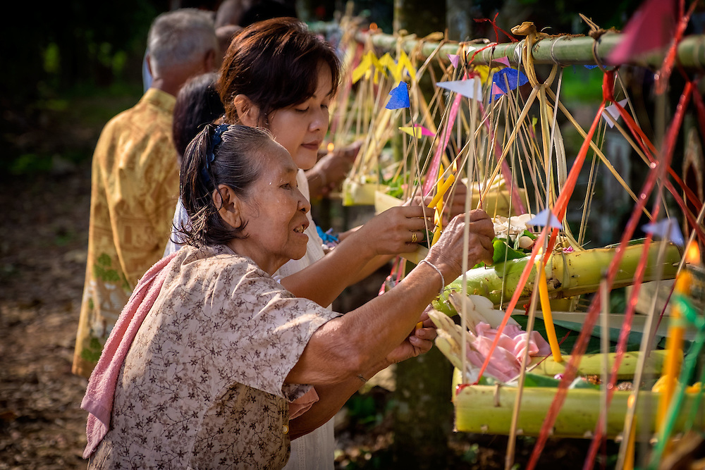Local women hang offering baskets made of banana trees, at a village home blessing and merit making ceremony in Nakhon Nayok, Thailand