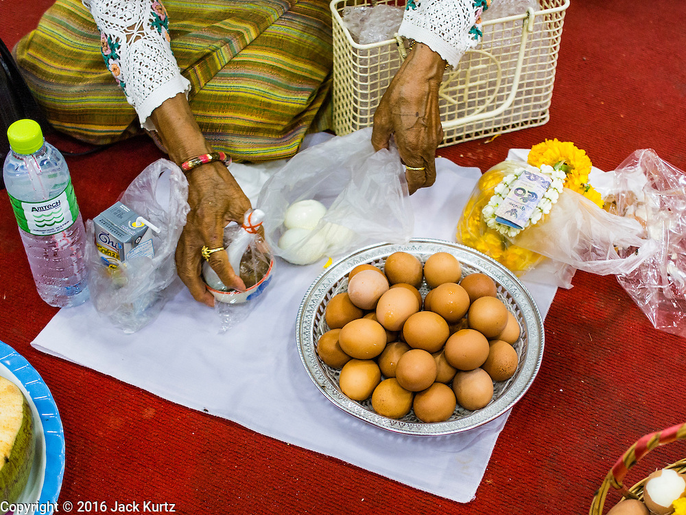 14 JANUARY 2016 - CHACHOENGSAO, CHACHOENGSAO, THAILAND: A woman prepares an offering of eggs at Wat Sothon. Wat Sothon, in Chachoengsao, is one of the largest Buddhist temples in Thailand. Thousands of people come to the temple every day to pray for good luck, they make merit by donating cooked eggs and cash to the temple. The temple dates from the Ayutthaya period (circa 18th century CE).           PHOTO BY JACK KURTZ