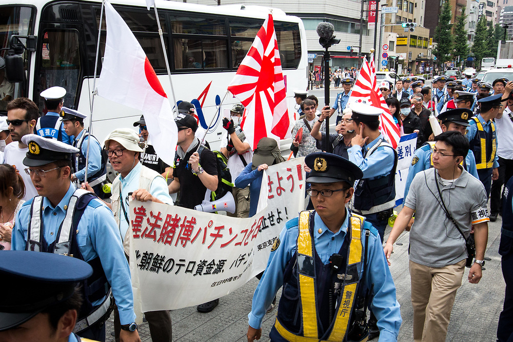 """TOKYO, JAPAN - JULY 16: Japanese nationalists holding Japanese flags took to the streets in a """"hate demonstration"""" in Akihabara, Tokyo, Japan on July 16, 2017. The nationalists faced off with anti-racist groups who mounted counter protests demanding an end to hate speech and racism in Japan. (Photo by Richard Atrero de Guzman/NUR Photo)"""
