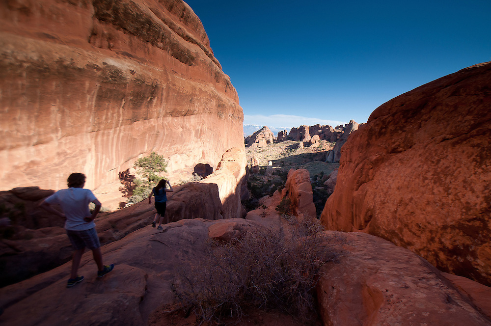 Hikers near Landscape Arch at Devils Garden, Arches National Park, Utah, US