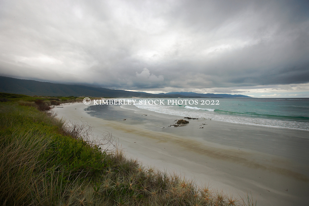 A storm rolls in over Templestowe Beach on Tasmania's east coast with Douglas Apsley National Park in the background.
