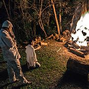 Durante la notte nella foresta la temperatura può scendere molto. alcuni membri si scaldano davanti al fuoco durante una breve pausa della cerimonia The night of São João. One of the most important ceremonies for Santo Daime's believers /