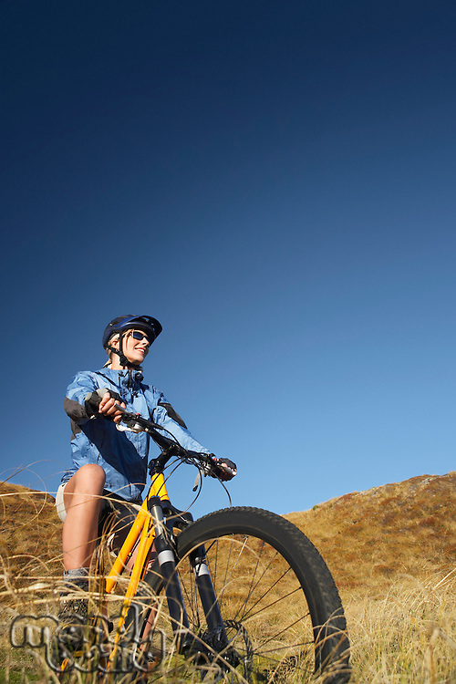 Woman riding bicycle in field