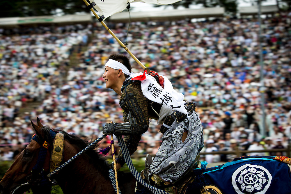 "MINAMISOMA, JAPAN - JULY 24 :  A young samurai horseman smiles after completing the race in the Kacchu-keiba (armed horse race) during the Soma Nomaoi festival at Hibarigahara field on Sunday, July 24, 2016 in Minamisoma, Japan. ""Soma-Nomaoi"" is a traditional festival that recreates a samurai battle scene from more than 1,000 years ago. (Photo: Richard Atrero de Guzman/NURPhoto)"