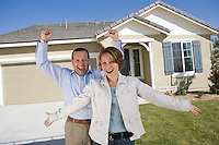 Mid-adult couple celebrating house ownership