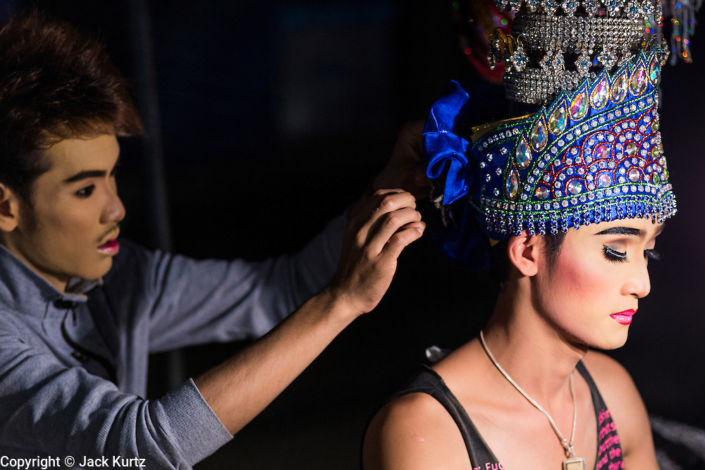 22 NOVEMBER 2013 - BANGKOK, THAILAND: A performer with the Prathom Bunteung Silp mor lam troupe gets help with his costume before a show in Bangkok. Mor Lam is a traditional Lao form of song in Laos and Isan (northeast Thailand). It is sometimes compared to American country music, song usually revolve around unrequited love, mor lam and the complexities of rural life. Mor Lam shows are an important part of festivals and fairs in rural Thailand. Mor lam has become very popular in Isan migrant communities in Bangkok. Once performed by bands and singers, live performances are now spectacles, involving several singers, a dance troupe and comedians. The dancers (or hang khreuang) in particular often wear fancy costumes, and singers go through several costume changes in the course of a performance. Prathom Bunteung Silp is one of the best known Mor Lam troupes in Thailand with more than 250 performers and a total crew of almost 300 people. The troupe has been performing for more 55 years. It forms every August and performs through June then breaks for the rainy season.     PHOTO BY JACK KURTZ