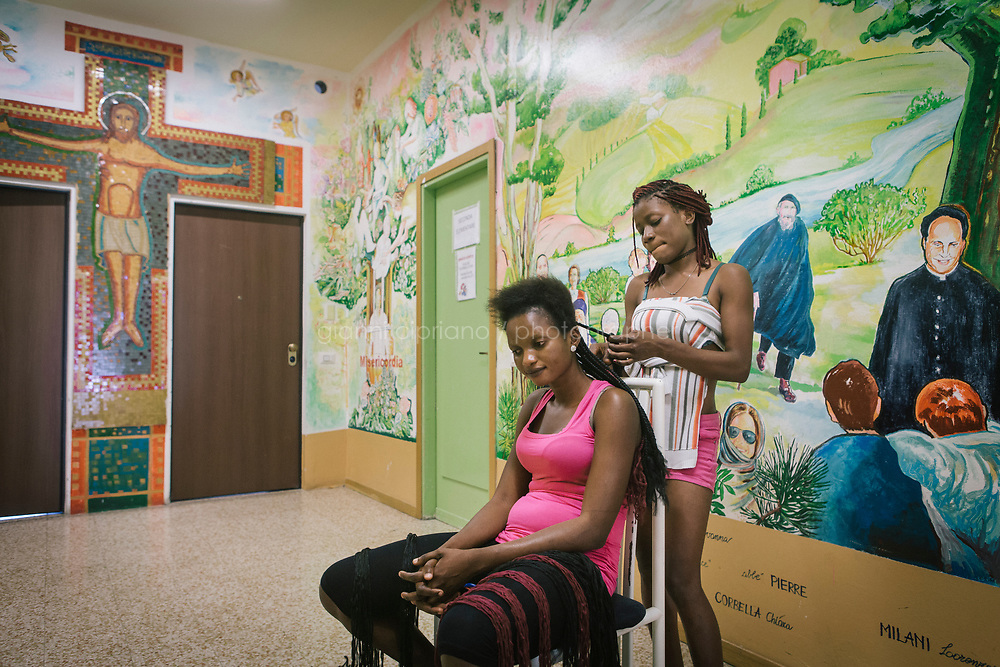 COMO, ITALY - 21 JUNE 2017: Sandra Obodo (left), 26), a Nigerian migrant, is seen here as one friend braids her hair  in the center ran by priest Giusto della Valle in Como, Italy, on June 21st 2017. Ms. Obodo said she crossed over from Libya nine months ago after escaping retribution murders at home and that a second boat she departed with was lost at sea.<br /> <br /> Residents of Como are worried that funds redirected to migrants deprived the town&rsquo;s handicapped of services and complained that any protest prompted accusations of racism.<br /> <br /> Throughout Italy, run-off mayoral elections on Sunday will be considered bellwethers for upcoming national elections and immigration has again emerged as a burning issue.<br /> <br /> Italy has registered more than 70,000 migrants this year, 27 percent more than it did by this time in 2016, when a record 181,000 migrants arrived. Waves of migrants continue to make the perilous, and often fatal, crossing to southern Italy from Africa, South Asia and the Middle East, seeing Italy as the gateway to Europe.<br /> <br /> While migrants spoke of their appreciation of Italy&rsquo;s humanitarian efforts to save them from the Mediterranean Sea, they also expressed exhaustion with the country&rsquo;s intricate web of permits and papers and European rules that required them to stay in the country that first documented them.