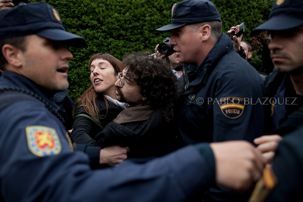 Riot police grab two an anti-eviction activists during a 'escrache' while they were going towards the house of Popular Party Deputy Mari Luz Prieto, on April 4, 2013 in Madrid, Spain. The Mortgage Holders Platform (PAH) and other anti evictions organizations are organizing 'escraches' for several weeks under the slogan 'There are lifes at risk' to claim the vote for a Popular Legislative Initiative (ILP) to stop evictions, regulate dation in payment and social rent outside Popular Party deputies' houses and offices..'Escraches' are form of peaceful public protest that was used in Argentine in 1995 to point to pardoned genocides of Argentenia's Dictatorship at their doorsteps.
