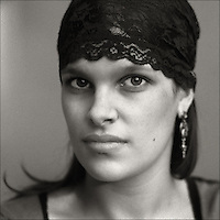 A woman with strong features wearing a black lace headband