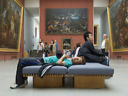 Louvre museum with an overwhelmed Japanese tourist resting on a bench
