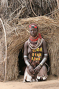 Africa, Ethiopia, Omo Valley, Daasanach tribe woman in front of hut