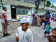 25 JUNE 2017 - BANGKOK, THAILAND: Children walk past Ton Son Mosque during Eid al-Fitr services in the mosque. Eid al-Fitr is also called Feast of Breaking the Fast, the Sugar Feast, Bayram (Bajram), the Sweet Festival or Hari Raya Puasa and the Lesser Eid. It is an important Muslim religious holiday that marks the end of Ramadan, the Islamic holy month of fasting. Muslims are not allowed to fast on Eid. The holiday celebrates the conclusion of the 29 or 30 days of dawn-to-sunset fasting Muslims do during the month of Ramadan. Islam is the second largest religion in Thailand. Government sources say about 5% of Thais are Muslim, many in the Muslim community say the number is closer to 10%.    PHOTO BY JACK KURTZ
