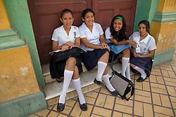 Central America, Nicaragua, Granada.  Teenage girls in school uniforms sitting on steps.