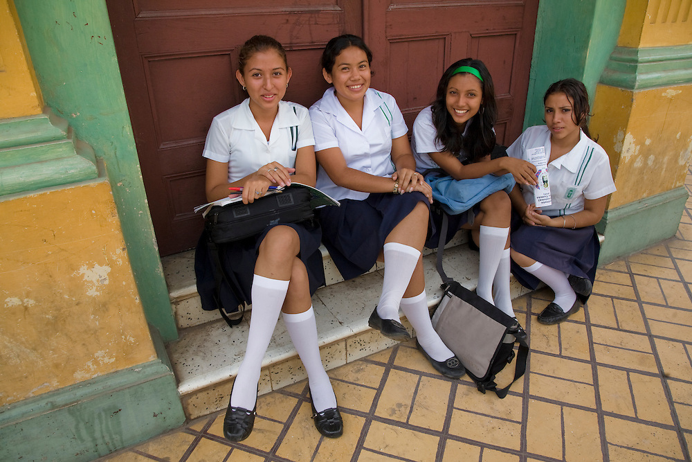 Central America, Nicaragua, Granada.  Teenage girls in school uniforms sitting on steps.