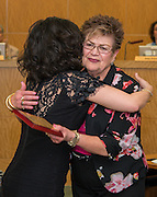 Juliet Stipeche hugs Elba Carrion during the Houston ISD Board of Trustees meeting, May 14, 2015.