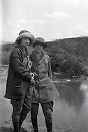 Two fashionable young women pose for a photo near a river during the 1920s or 1930s. The hats are Cloche hats which were popular in the 1920s.