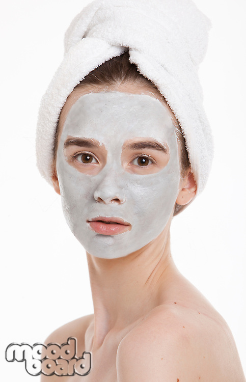 Portrait of young woman with face pack and towel wrapped around head against white background