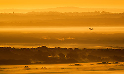 © Licensed to London News Pictures. 03/10/2016. Dorking, UK. An aircraft takes off from Gatwick airport - seen from near Leith Hill at dawn. Sunshine and warm autumn weather are forecast for today. Photo credit: Peter Macdiarmid/LNP