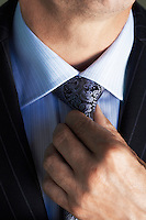 Middle-aged businessman in full suit adjusting tie  mid section