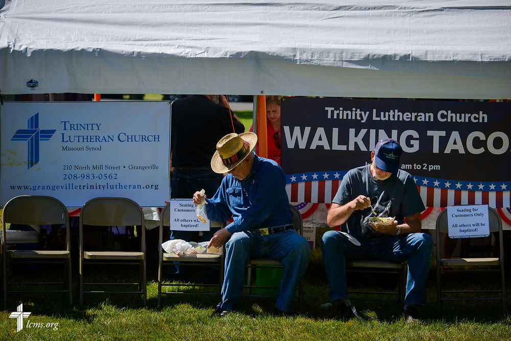 Brothers Dick and Charles Spengler eat at the Trinity Lutheran Church, Grangeville, Idaho, walking tacos tent at the Grangeville Border Days Independence Day celebration and parade on Tuesday, July 4, 2017, in Grangeville. LCMS Communications/Erik M. Lunsford