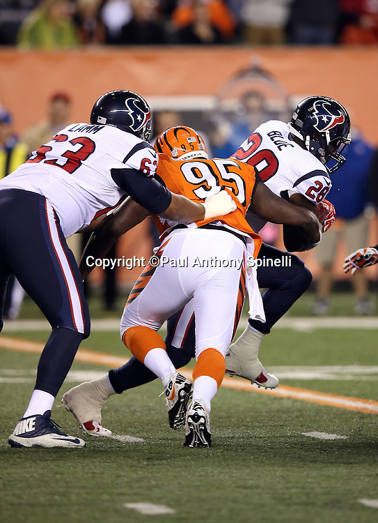 Houston Texans tackle Kendall Lamm (63) blocks while Houston Texans running back Alfred Blue (28) gets tackled by Cincinnati Bengals defensive end Wallace Gilberry (95) as he runs the ball in the first quarter during the 2015 week 10 regular season NFL football game against the Cincinnati Bengals on Monday, Nov. 16, 2015 in Cincinnati. The Texans won the game 10-6. (©Paul Anthony Spinelli)