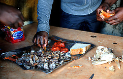 Cape Town-180906 Customers enjoying smiley Sheep head with bread and tomato in Khayelitsha. The Sheep head also know as Smiley is very popular in the township it used to be cooked only if there was traditional cremony nowadays there are many places that clean and sell this delicacy,cooked or uncooked Sheep head cost R70 and half R35 Pictures Ayanda Ndamane/African/news/agency ANA