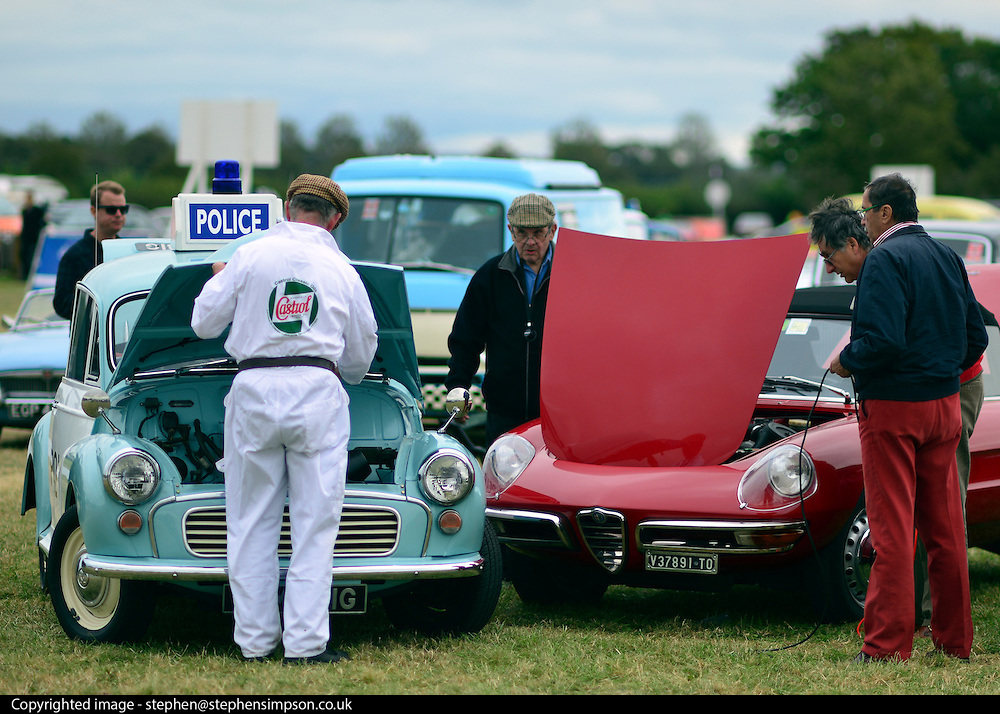 © Licensed to London News Pictures. 16/09/2012. Goodwood, UK . A car is jump started by a vintage police car. People enjoy the atmosphere at the 2012 Goodwood Revival. The event recreates the glorious days of motor racing and participants are encouraged to dress in period dress. Photo credit : Stephen Simpson/LNP