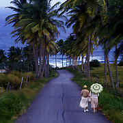 Two local residents take a stroll to the sea near Bathsheba, Barbados.