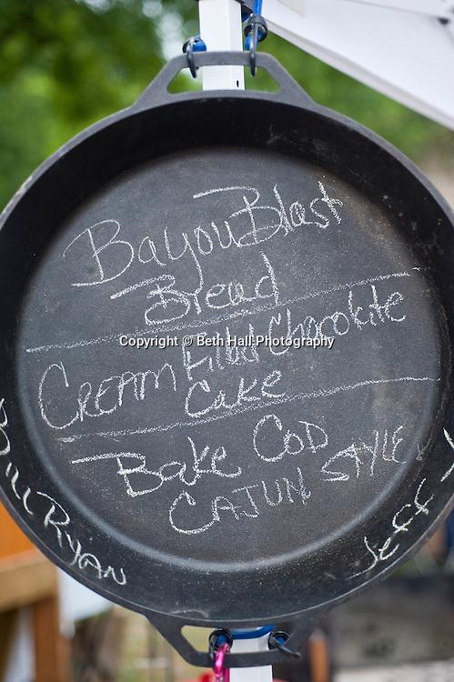 A menu is written in chalk in a dutch oven at Elk Fest in Jasper, Arkansas.