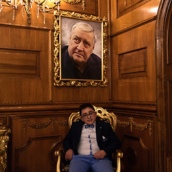 "A guest poses in the hall of ""Grand Hotel La Sonrisa"", below the photo of Mario Merola."