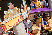 05 MAY 2010 - BANGKOK, THAILAND: People sit under a photo of the King while they wait for Thai King Bhumibol Adulyade to pass them Wednesday, May 5. Wednesday was Coronation Day in Thailand, marking the 60th anniversary of the coronation of Thai King Bhumibol Adulyade, also known as Rama IX. He is the world's longest serving current head of state and the longest reigning monarch in Thai history. He has reigned since June 9, 1946 and his coronation was on May 5, 1950, after he finished his studies. The King is revered by the Thai people. Thousands lined the streets around the Grand Palace hoping to catch a glimpse of the King as his motorcade pulled into the palace. The King has been hospitalized since September 2009, making only infrequent trips out of the hospital for official functions, like today's ceremonies.   PHOTO BY JACK KURTZ