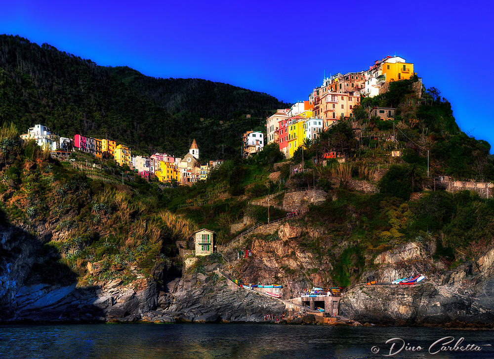 &ldquo;Corniglia from the sea aboard the Angelina Dada&rdquo;&hellip;<br /> <br /> I began my daily journey at the northern most town of Monterosso and took the train to the southernmost town of Riomaggiore. I sailed up the coast photographing each Cinque Terre town along the way aboard the Angelina Dada. Upon arriving back home in Monterosso, soft light illuminated the sky and azure sea of the Mediterranean convincing me to sail all the way back to Riomaggiore with my gracious guides Claudio and Eddie of &quot;Cinque Terre dal Mare&quot; sailing excursions. We arrived just in time for a perfect sunset. After a nice dinner...I caught the last train at midnight back home to Monterosso. A very long day, but worth every minute!  This image of Corniglia, the only Cinque Terre town not directly on the sea&hellip;was taken at the beginning of the journey from Riomaggiore.  The two image panorama of this tiny village seems to snuggle into the Cliffside basking in the evening sunlight.