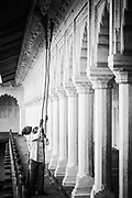 Agra Fort, tradesmen clean the fort using long brooms. Black and white.