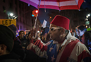 A man wearing a traditional Moroccan jellaba with an American flag motif at an Anti-Trump rally in Lower Manhattan, after the Trump administration implemented a ban on entry to citizens of 7 Muslim-majority nations into the United States.  New York, New York, USA.  29 January 2017