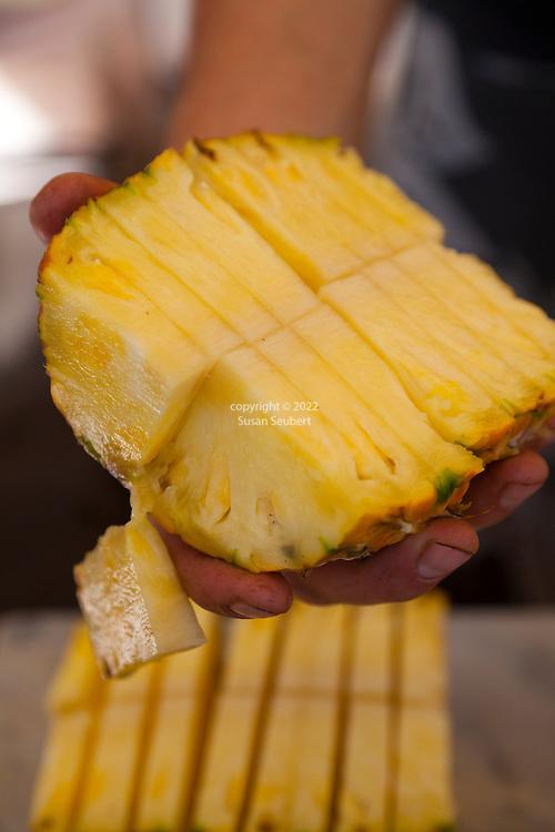 Maui, Hawaii.  Freshly cut pineapple at the Ono Farm road side stand in Hana, Maui.