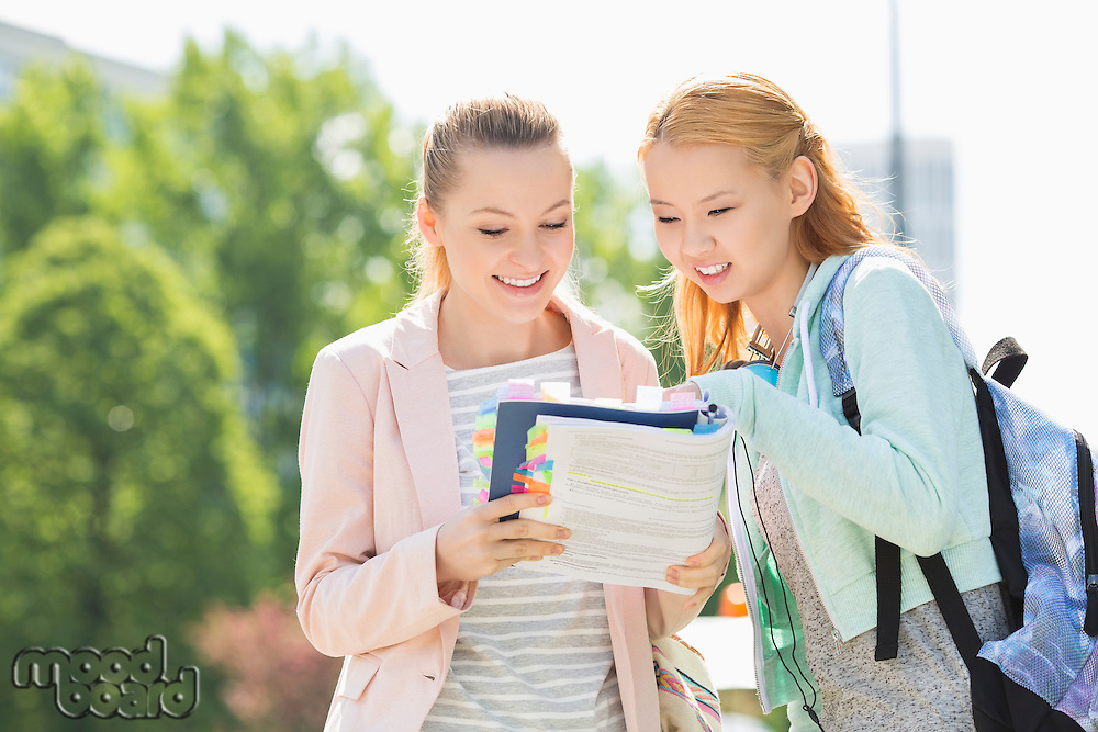 Happy young female students reading book at college campus