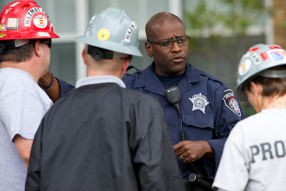 A police officer speaks with the haz-mat crew outside the apartment where a second Ebola patient has been reported in Dallas, Texas on October 13, 2014. (Cooper Neill for The New York Times)
