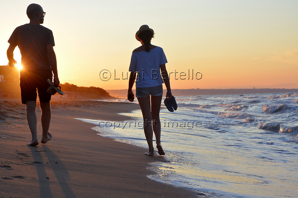 Adult young couple silhouette  strolls on a sandy beach at sunset.