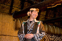 An Ainu man entertains the crowd, dressed in traditional clothing.