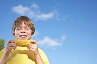 Portrait of boy (7-9) eating corn on the cob