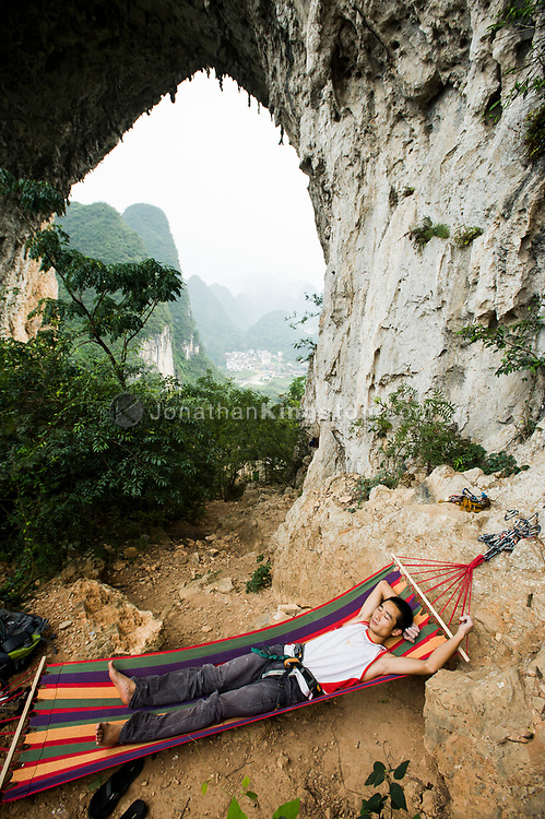 A rock climber sleeps in a colorful hammock under Moon Hill near Yangshuo, China  (Model Released, Li Shengiang).